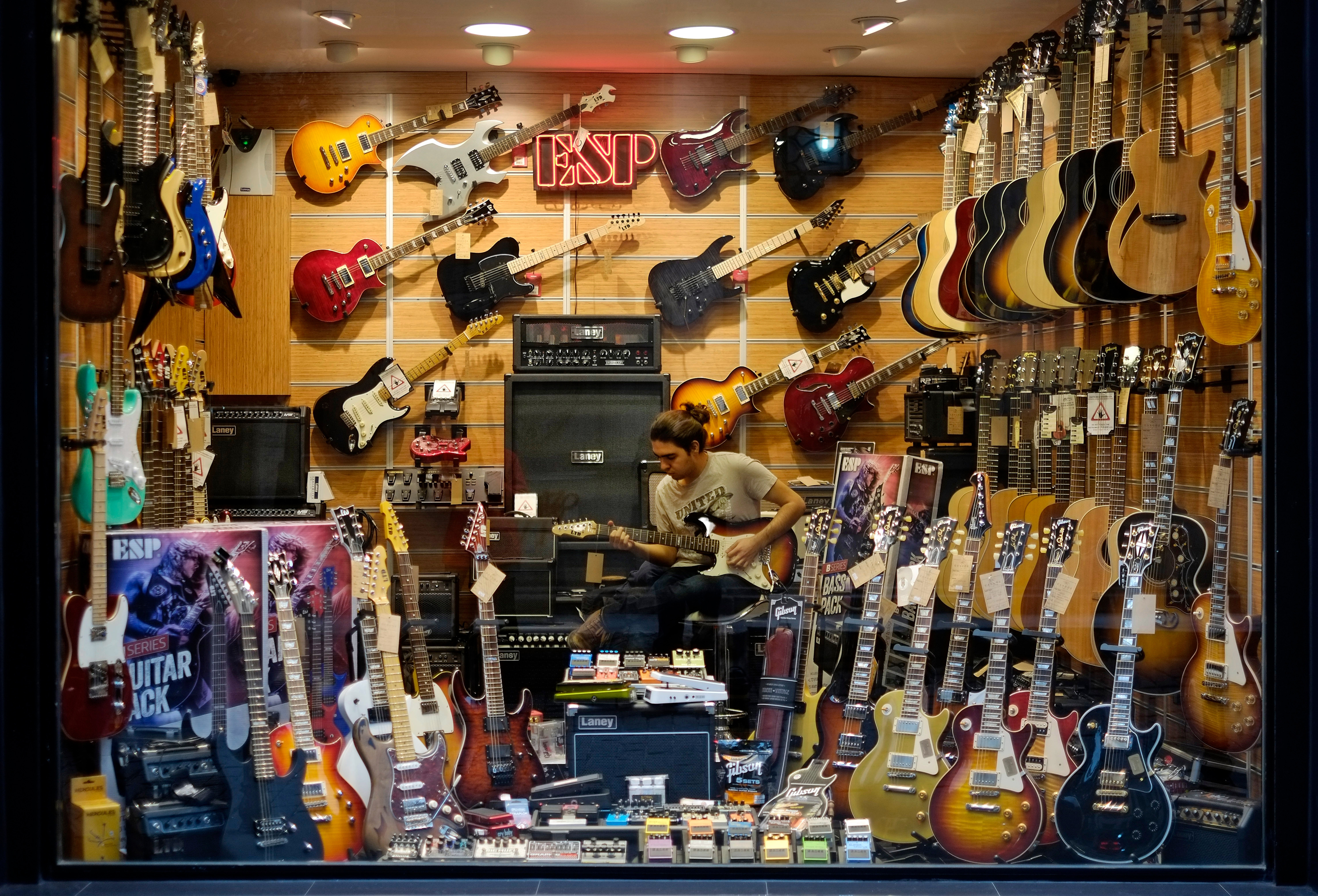 how to make er diagram amazing s musician record online home decorating services A man plays a guitar inside a musical instrument shop in Istanbul.