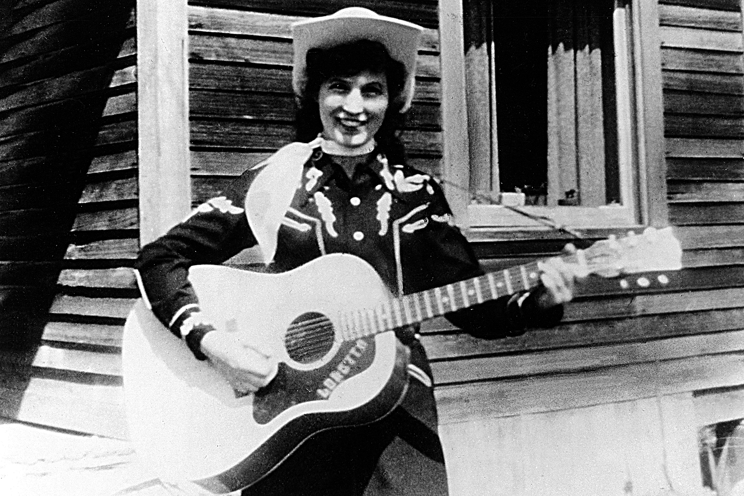 Loretta Lynn holds her acoustic guitar as she poses for a portrait wearing  a cowboy hat 70da9cd2d623