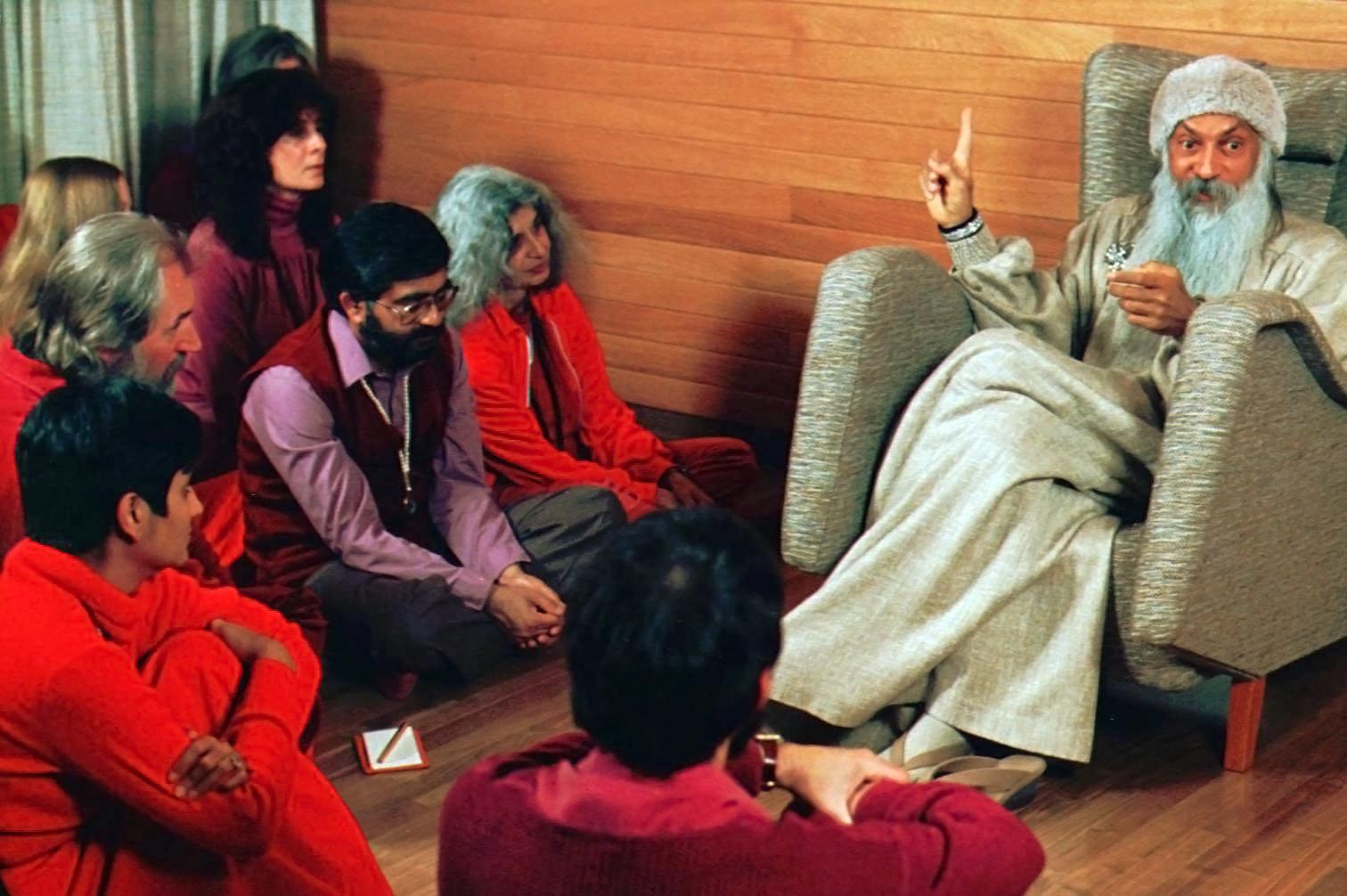 Bhagwan Shree Rajneesh, right, speaks with his disciples in Rajneeshpuram,  Oregon.