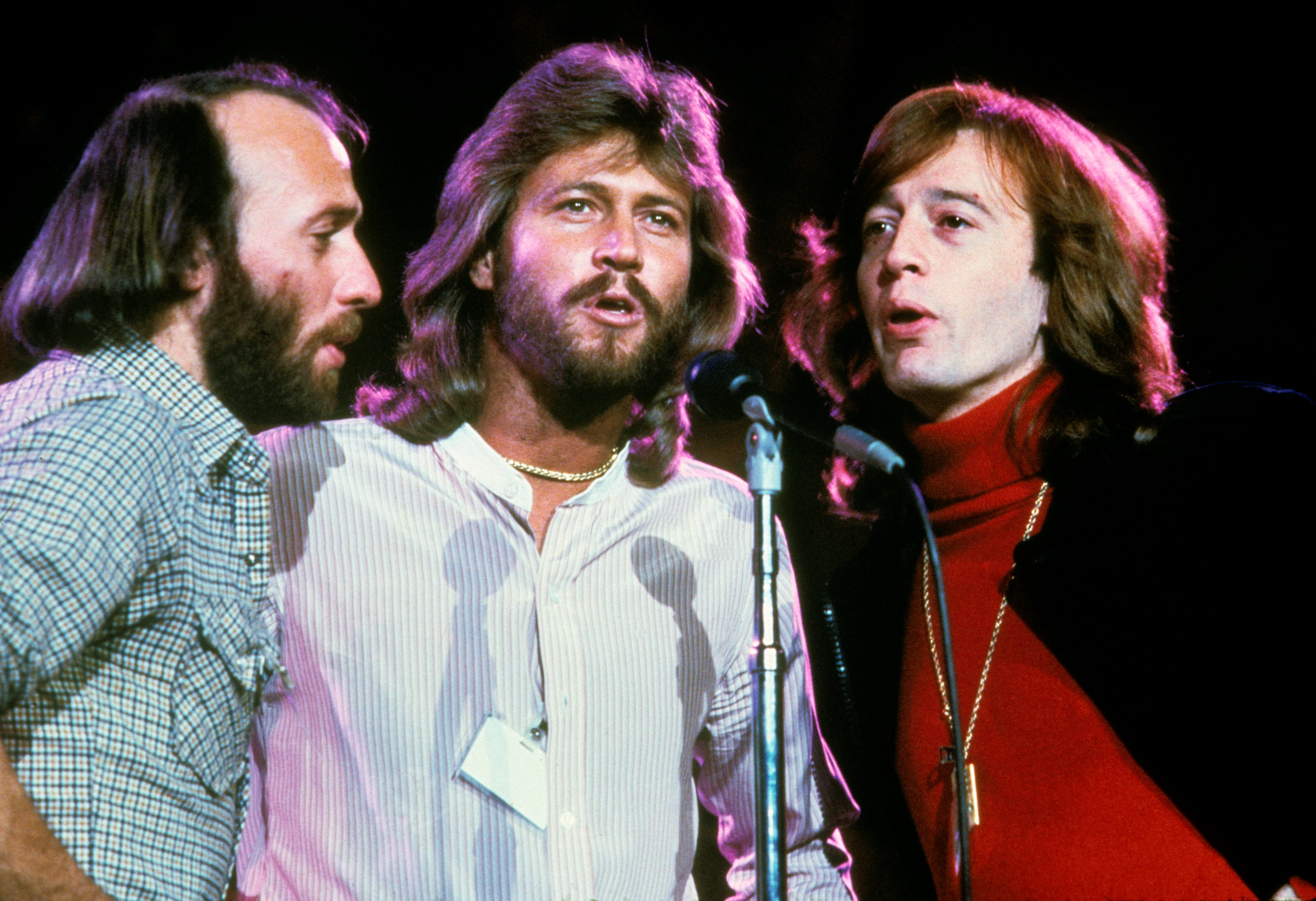 48fa8b8db The Bee Gees harmonize at one microphone while performing on stage at the  UNICEF A Gift of Song concert held at the United Nations General Assembly,  ...