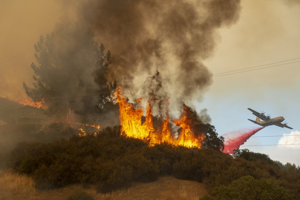 July 30, 2018 - Lakeport, California, U.S. - Fire retardant is dropped near a home as the Mendocino Complex Fire burns off of Keck Road, just west of Lakeport, Calif., on Monday. More than 10,000 structures are threatened in Lake and Mendocino Counties as the Mendocino Complex Fire continues to burn. (Credit Image: © Jose Luis Villegas/TNS via ZUMA Wire)