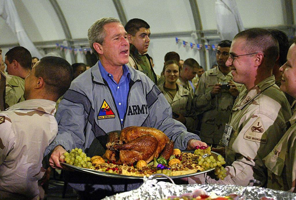 BAGHDAD, IRAQ: US President George W. Bush carries a platter of turkey and fixings as he visits US troops for Thanksgiving in Baghdad, 27 November, 2003. Bush made the Thanksgiving visit to troops in Baghdad under the greatest secrecy and security. News of his trip was not even released until Air Force One had already left Iraq. Television reports said US authorities would have called off the visit had news been leaked in advance.AFP PHOTO/Anja NIEDRINGHAUS/POOL (Photo credit should read ANJA NIEDRINGHAUS/AFP/Getty Images)