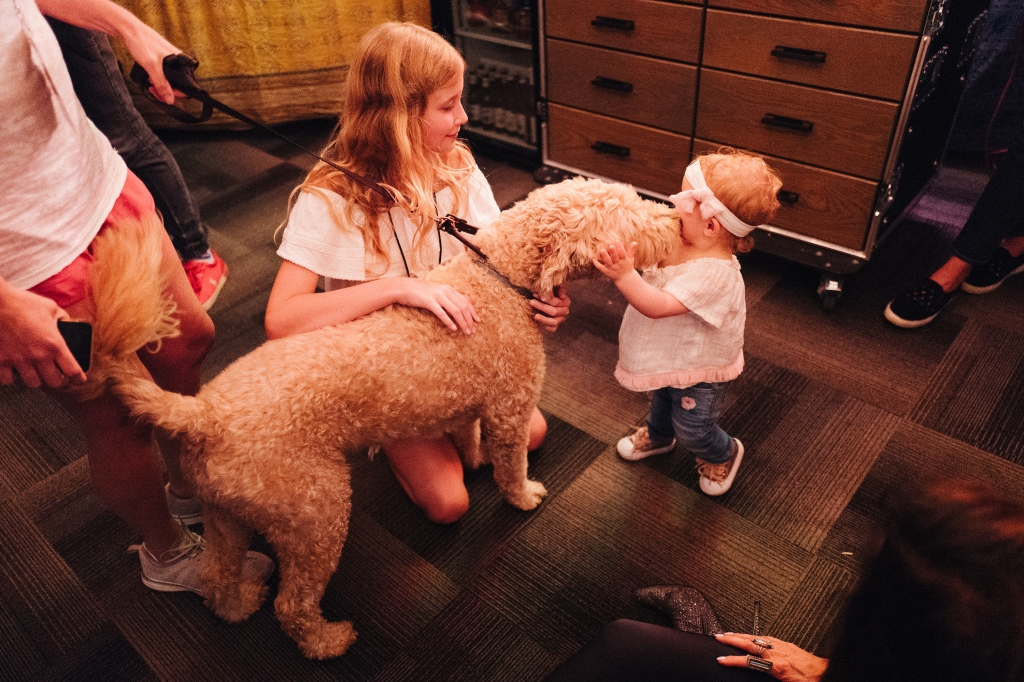 Phillip Sweet's daughter Penelopi and Kimberly Schlapman's daughter Dolly get some backstage affection from the Sweet family's goldendoodle Disney.
