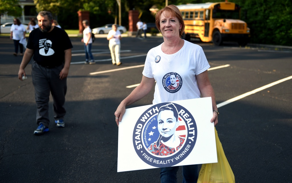 Billie Winner-Davis, mother of Reality Winner, carries a sign in support of her daughter outside the Lincoln County Law Enforcement Center in Lincolnton, Ga., Sunday evening June 3, 2018. Winner-Davis and other supporters gathered outside the jail a year after Reality Winner's arrest. Winner worked for the national security contractor Pluribus International at Fort Gordon in Georgia when she was charged last June with mailing a classified U.S. report to an unidentified news organization. (Michael Holahan/The Augusta Chronicle via AP)