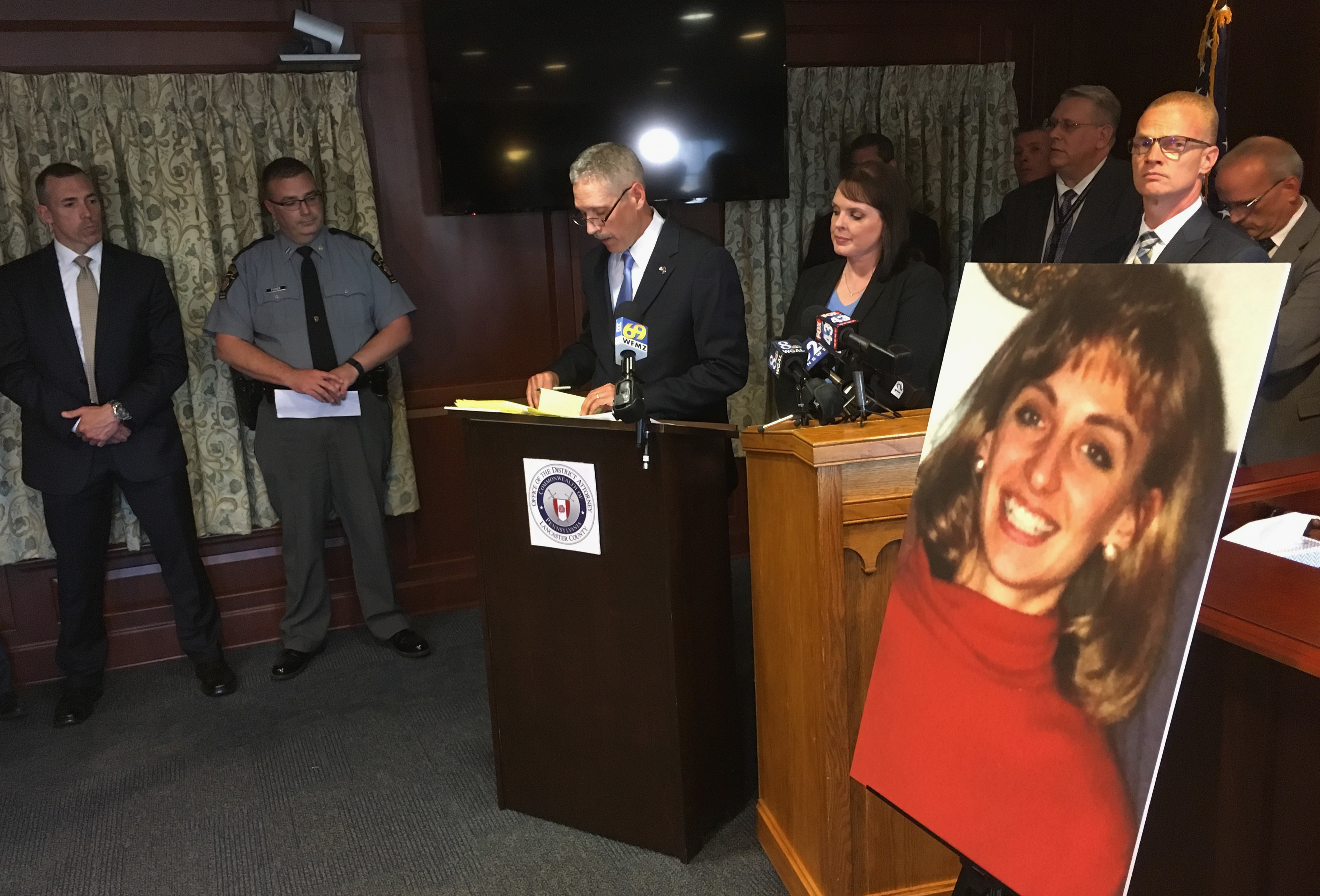 Lancaster County District Attorney Craig Stedman announces charges in a 1992 cold case killing during a news conference at the Lancaster County Courthouse in Lancaster, Pa., Monday, June 25, 2018. A family photo of the victim, Christy Mirack, is seen at right. A popular DJ in Pennsylvania has been charged in the 1992 killing of Mirack, an elementary school teacher who was sexually assaulted, beaten and strangled in her home as she was getting ready for work. (AP Photo/Mark Scolforo)