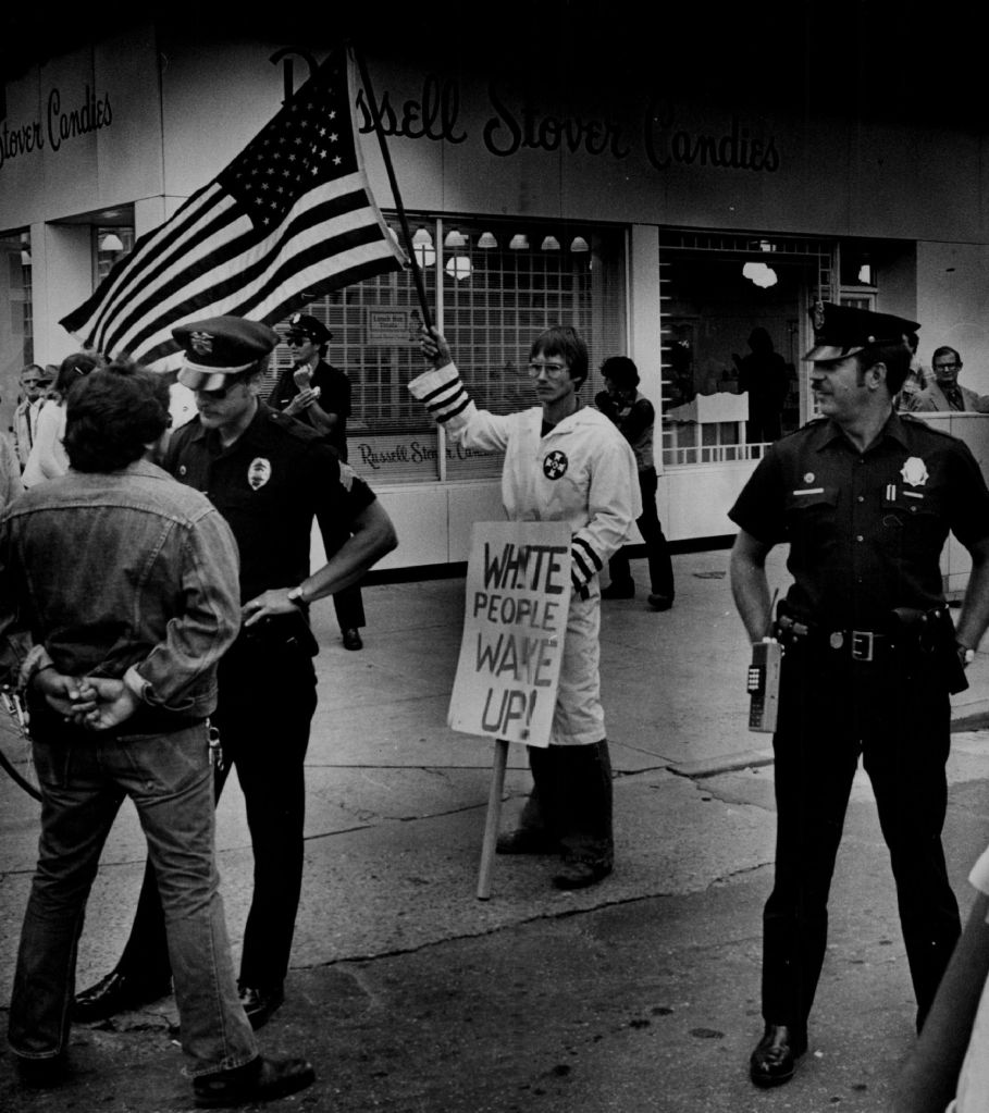 SEP 14 1979, SEP 15 1979; Ku Klux Klan Denver; Klansman Spells out his feelings; Denver policeman protect a flag-waving member of the Ku Klux Klan at 16th street and Court place about 11:45 a.m. Friday during a Chicano march through downtown Denver Kicking off festivities for Mexican Independence Day, celebrated Sunday. One of the marchers in confronted by a policeman, left, as he attempts to approach the Klansman. Shortly after, unidentified Klansman rolled up his sign and flag and left.; (Photo By Duane Howell/The Denver Post via Getty Images)