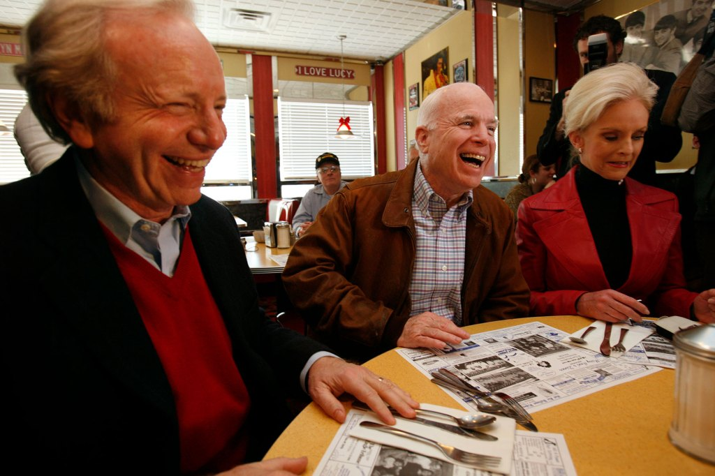 John McCain campaigns with Sen. Joseph Lieberman, left, at Mary Ann's Diner in Derry, NH on January 2, 2008, the day before the Iowa caucuses. To the right is McCain's wife, Cindy.