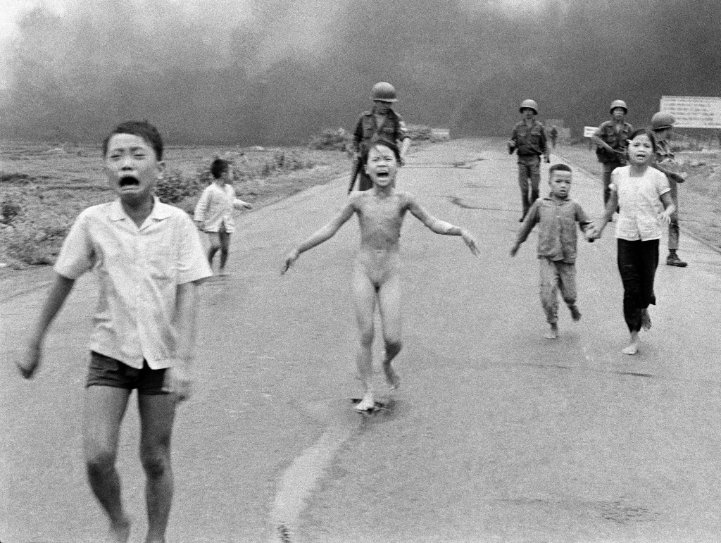 "Taken by Huynh Cong ""Nick"" Ut, South Vietnamese forces follow behind terrified children, including 9-year-old Kim Phuc, center, as they run down Route 1 near Trang Bang after an aerial napalm attack on suspected Viet Cong hiding places. On, precisely 43 years later, Nick Ut returned to the same place to capture his memories with a tool from an entirely different era, a 4-ounce iPhone 5 equipped with the ability to send photos to the world in the blink of a digital eyeVietnam Photographer's Return, Trang Bang, Vietnam"