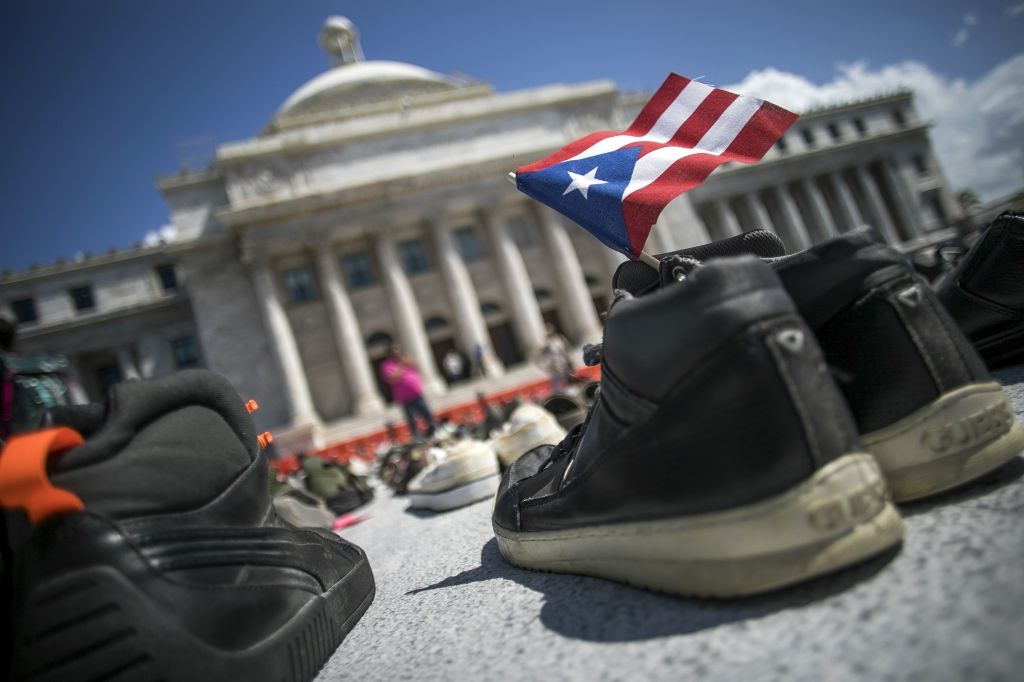 A Puerto Rican flag stands inside a pair of shoes displayed outside the Capitol building during a protest against the government's reporting of the death toll from Hurricane Maria in San Juan, Puerto Rico, on Friday, June 1, 2018. Hurricane Maria probably killed about 5,000 people in Puerto Rico last year even though the official count remains at just 64, according to a Harvard University study released Tuesday. Photographer: Xavier Garcia/Bloomberg via Getty Images