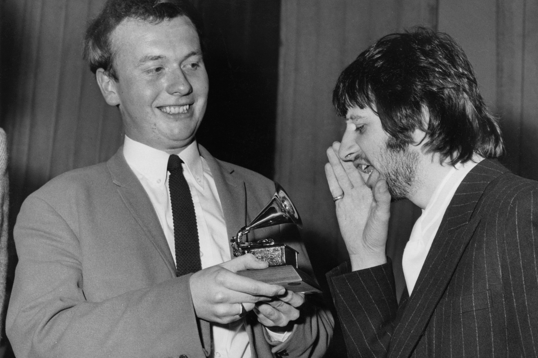 Drummer Ringo Starr of English rock band the Beatles congratulates EMI recording studio audio engineer Geoff Emerick (left) on his Grammy Award at the EMI studios in London, 7th March 1968. Emerick engineered the sound on the Beatles' album 'Sgt. Pepper's Lonely Hearts Club Band'. (Photo by Monti Spry/Central Press/Hulton Archive/Getty Images)