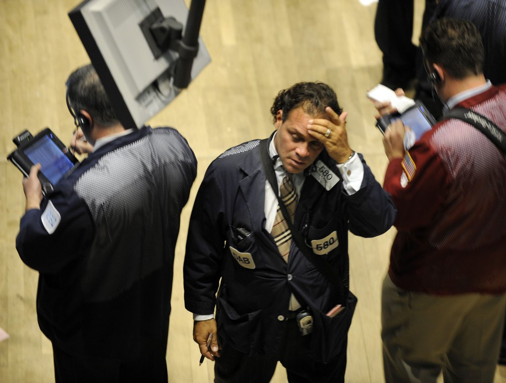 A trader on the floor of the New York Stock Exchange holds his head as he walks off the floor September 29, 2008. Wall Street blue-chip stocks suffered their worst single-day point decline Monday as markets went into convulsions after US lawmakers rejected a massive rescue of the financial system. The Dow Jones Industrial Average sank 777.68 points (6.98) percent to close at 10,365.45 in its biggest single-day point decline ever. AFP PHOTO/ TIMOTHY A. CLARY (Photo credit should read TIMOTHY A. CLARY/AFP/Getty Images)