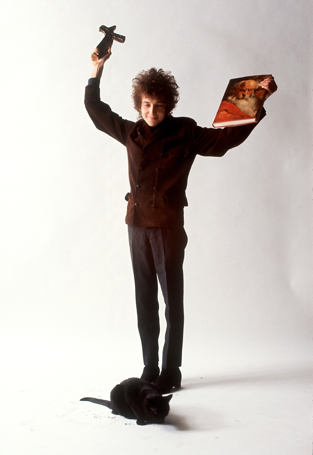 "When Dylan arrived at his New York studio, Schatzberg handed him props and encouraged him to pose however he felt comfortable. ""These were just things I had around the studio,"" he says. ""I would just take something and see what he would do with it."" [Note: In this photo he's wearing the same coat that appears on the cover of Blonde on Blonde and John Wesley Harding.]"