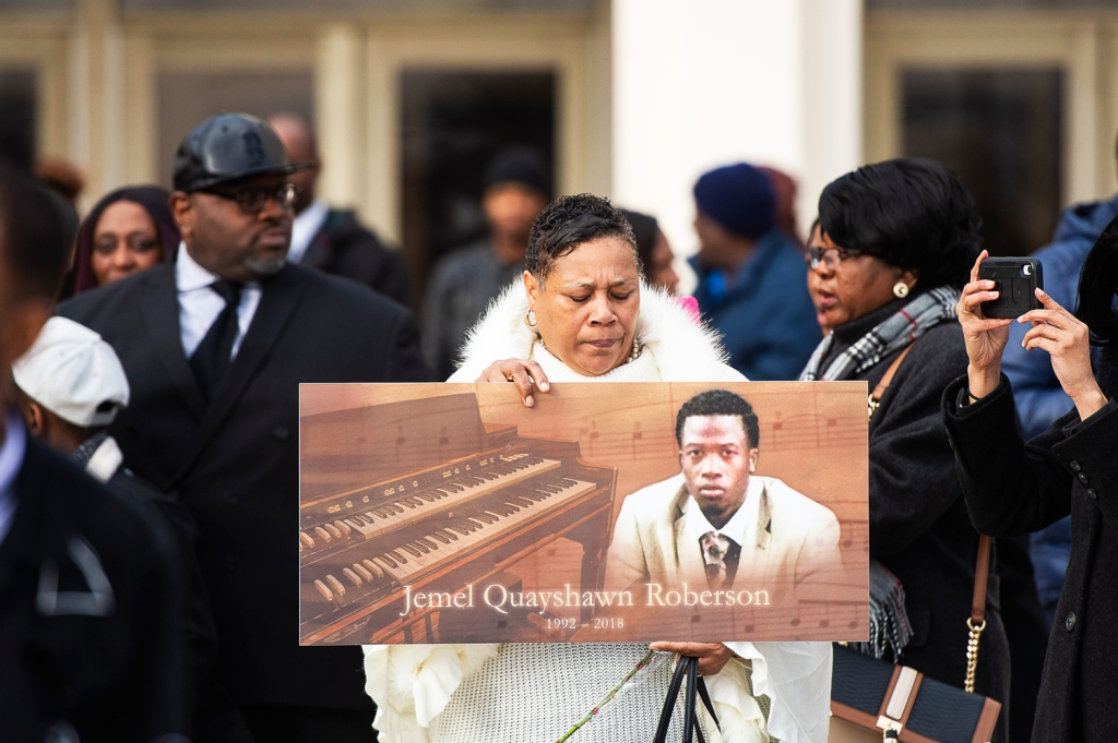 A woman holds up a sign with Jemel Roberson's image at his funeral, Saturday, Nov. 8, 2018