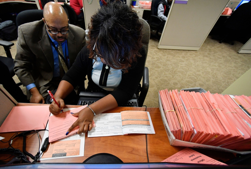 A Fulton County election worker counts provisional ballots, in Atlanta. Malfunctioning voting machines, missing power cords, and hours-long lines at the polls are being scrutinized in Georgia, where the governor's race is still undecided as votes are still being talliedElection 2018 Georgia Voting Problems, Atlanta, USA - 07 Nov 2018