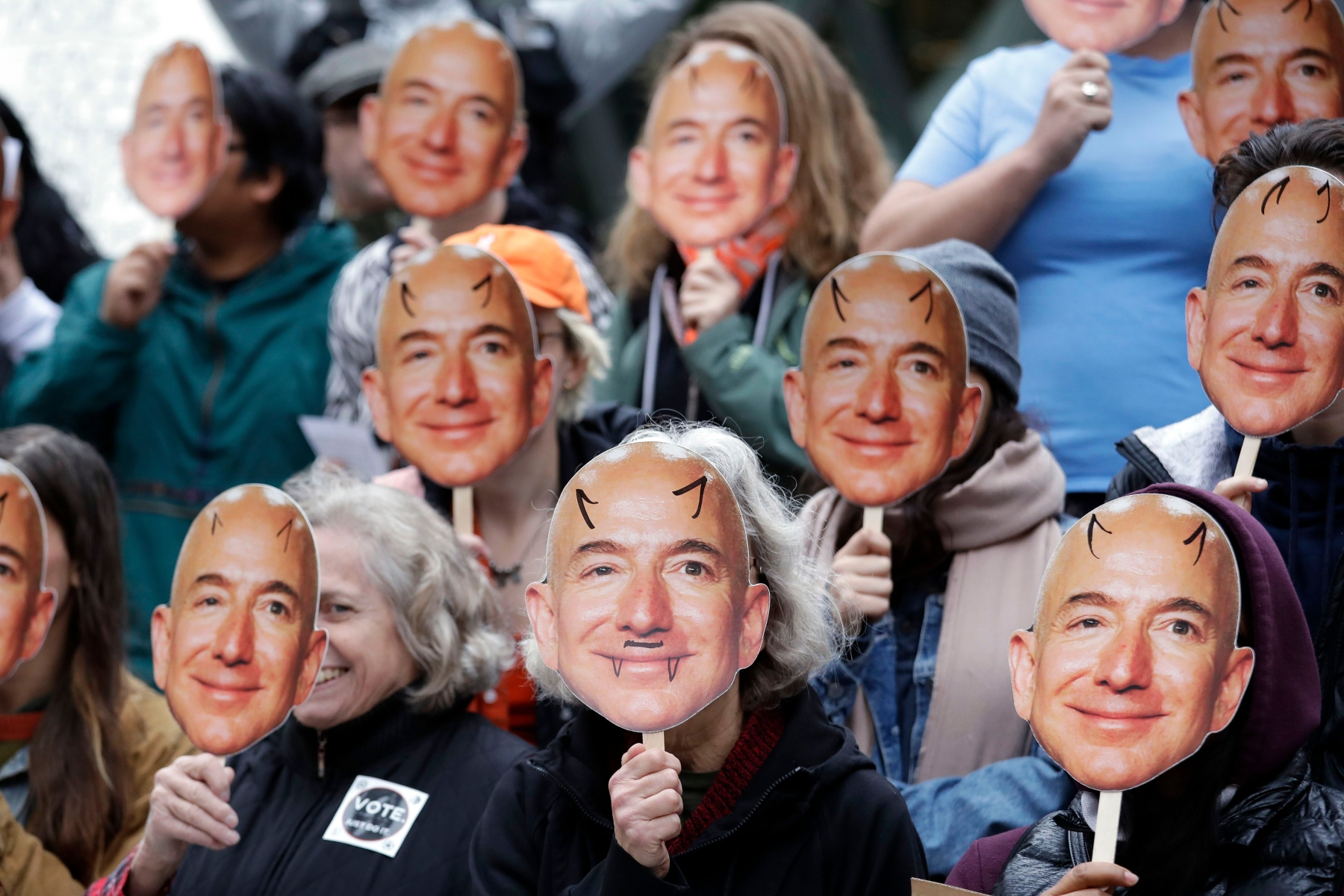 """Demonstrators hold images of Amazon CEO Jeff Bezos near their faces during a Halloween-themed protest at Amazon headquarters over the company's facial recognition system, """"Rekognition,"""", in Seattle. Protesters said that they were there in support of hundreds of Amazon employees who have signed a letter asking the company to stop marketing their facial recognition software to ICE and to drop its contract with software company Palantir and to law enforcement agenciesAmazon Protest, Seattle, USA - 31 Oct 2018"""