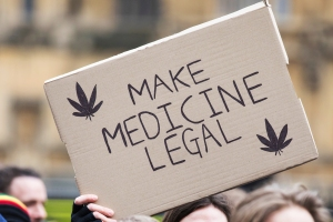 A man holds a sign with cannabis leaves on it which reads 'Make Medicine Legal' at a protest opposite Parliament in support of the legalisation of cannabis for medicinal use while MPs debate the issue in The House of Commons.United Patients Alliance legalise cannabis rally, London, UK - 23 Feb 2018