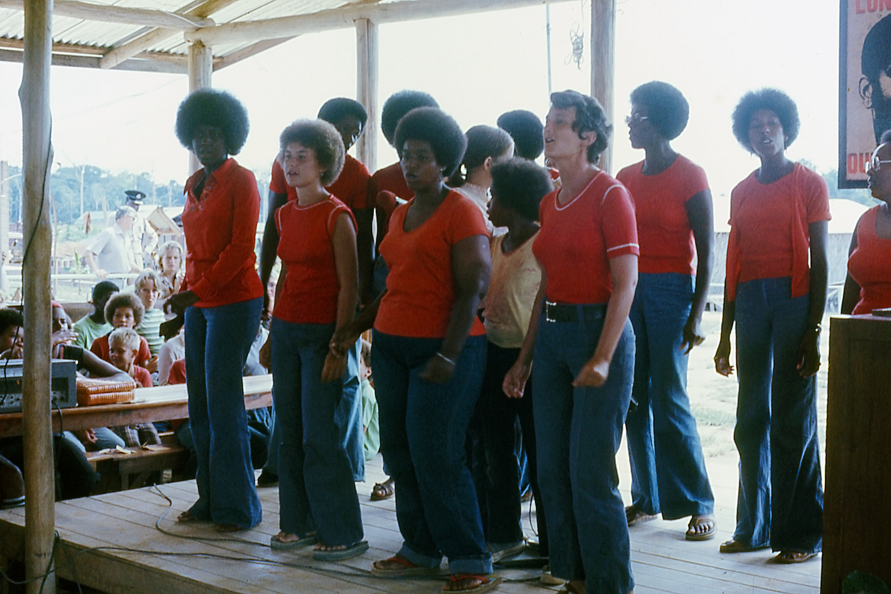 Peoples Temple members singing in pavilion, Jonestown, Guyana, circa 1977-1978 (l to r, front row) unidentified, Erin Leroy, Shirley Baisey, Laura Johnston, (r, back row) Anita James
