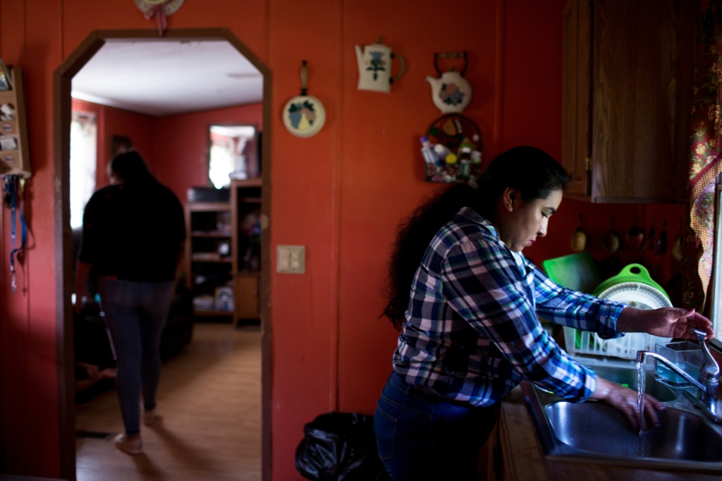 October 8, 2018. Morristown Tennessee. Alma Mercado prepares to cook lunch for her family after a day of mowing lawns for extra money after she lost her job in the plant. After a major ICE raid at the Southeastern Provisions slaughterhouse in Bean Station, TN, the latino community in the surrounding area of Morristown and Grainger County has been deeply affected by fear, job loss, and deportations of family members or pending deportation proceedings. (Natalie Keyssar for Rolling Stone)
