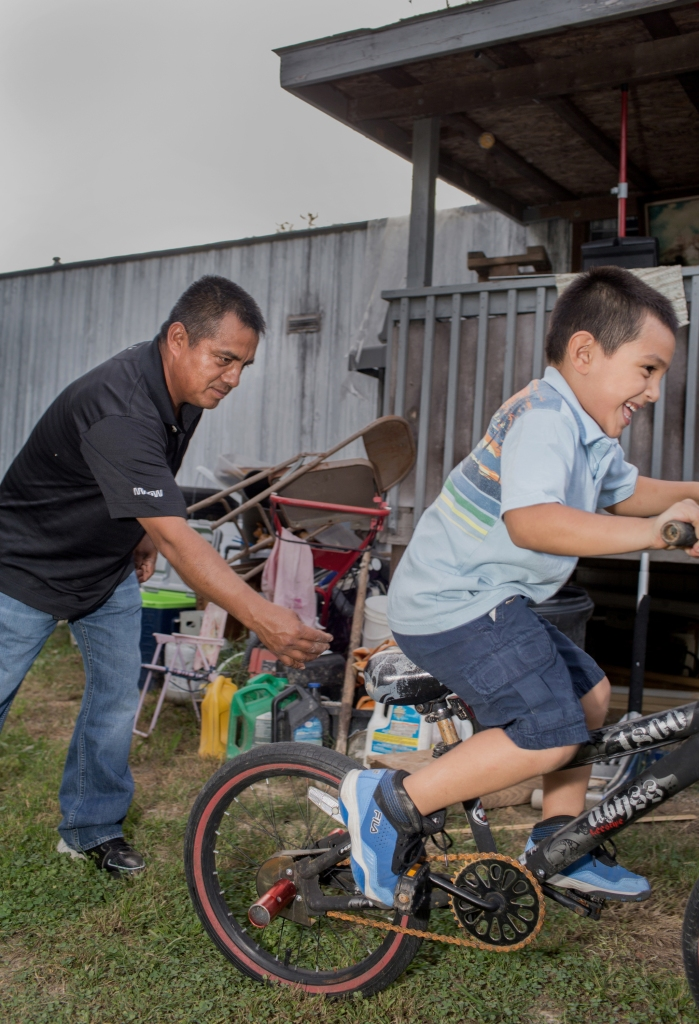 October 8, 2018. Morristown Tennessee. Alberto Librado plays with his son Abdiel after adjusting the handle bars and adding rear pegs for him. Alberto was detained in the raid and is awaiting his court date.After a major ICE raid at the Southeastern Provisions slaughterhouse in Bean Station, TN, the latino community in the surrounding area of Morristown and Grainger County has been deeply affected by fear, job loss, and deportations of family members or pending deportation proceedings. (Natalie Keyssar for Rolling Stone)