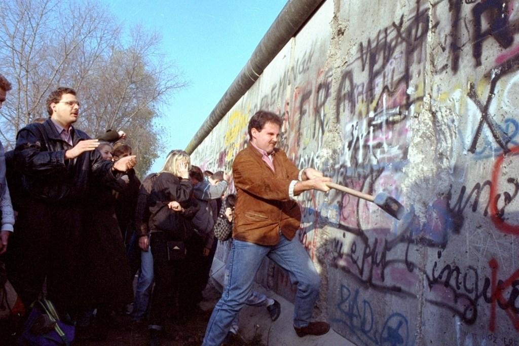 An unidentified West Berliner swings a sledgehammer, trying to destroy the Berlin Wall near Potsdamer Platz,, where a new passage was opened nearbyFALL OF BERLIN WALL, BERLIN, Germany