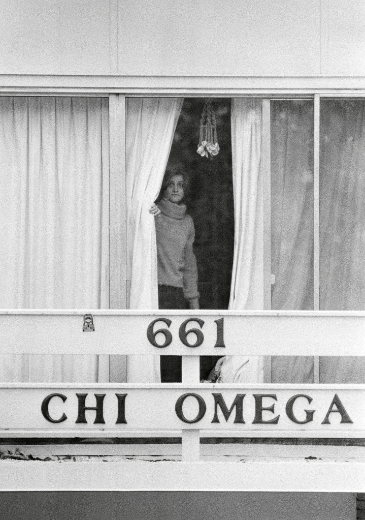 An unidentified woman peers through drapes on the 2nd story balcony of the Chi Omega sorority house at Florida State University in Tallahassee, Fla., . Two sorority sisters, Margaret Bowman and Lisa Levy, were brutally beaten to death with the assailant leaving 3 others injured early Sunday morningTed Bundy Victims 1978, Tallahassee, USA