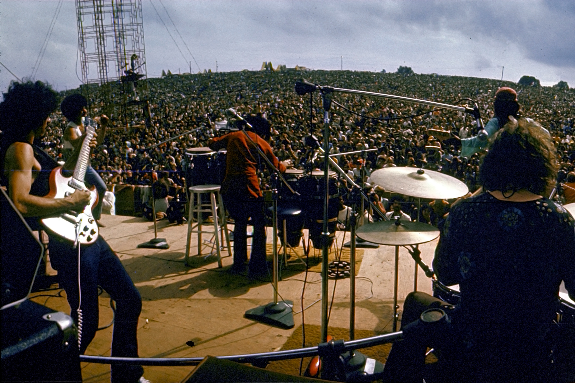 Mexican guitarist Carlos Santana (left) and his band perform on stage to a huge audience at the Woodstock Music