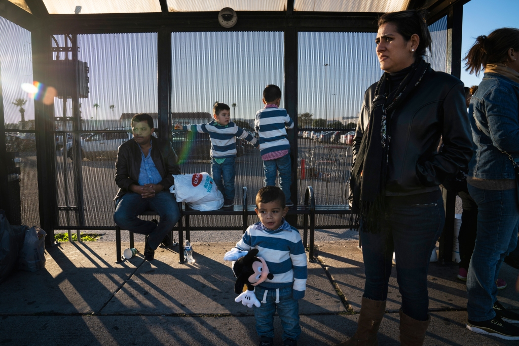 Ignacio Ramos, left, and his wife Marcela Morales, right, from Tabasco, wait for a cab to take them to the Hidalgo-Reynosa International Bridge along with their three kids and their grandmother in McAllen, Tex. on Dec. 9, 2018. Ramos' work took him to Reynosa and he decided to bring his family so they could go shopping to McAllen, Tex.Verónica G. Cárdenas for Rolling Stone