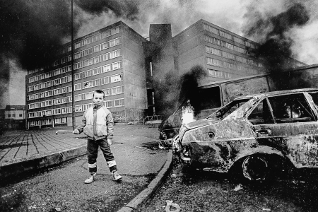 Boy and flaming car outside Divis flats.