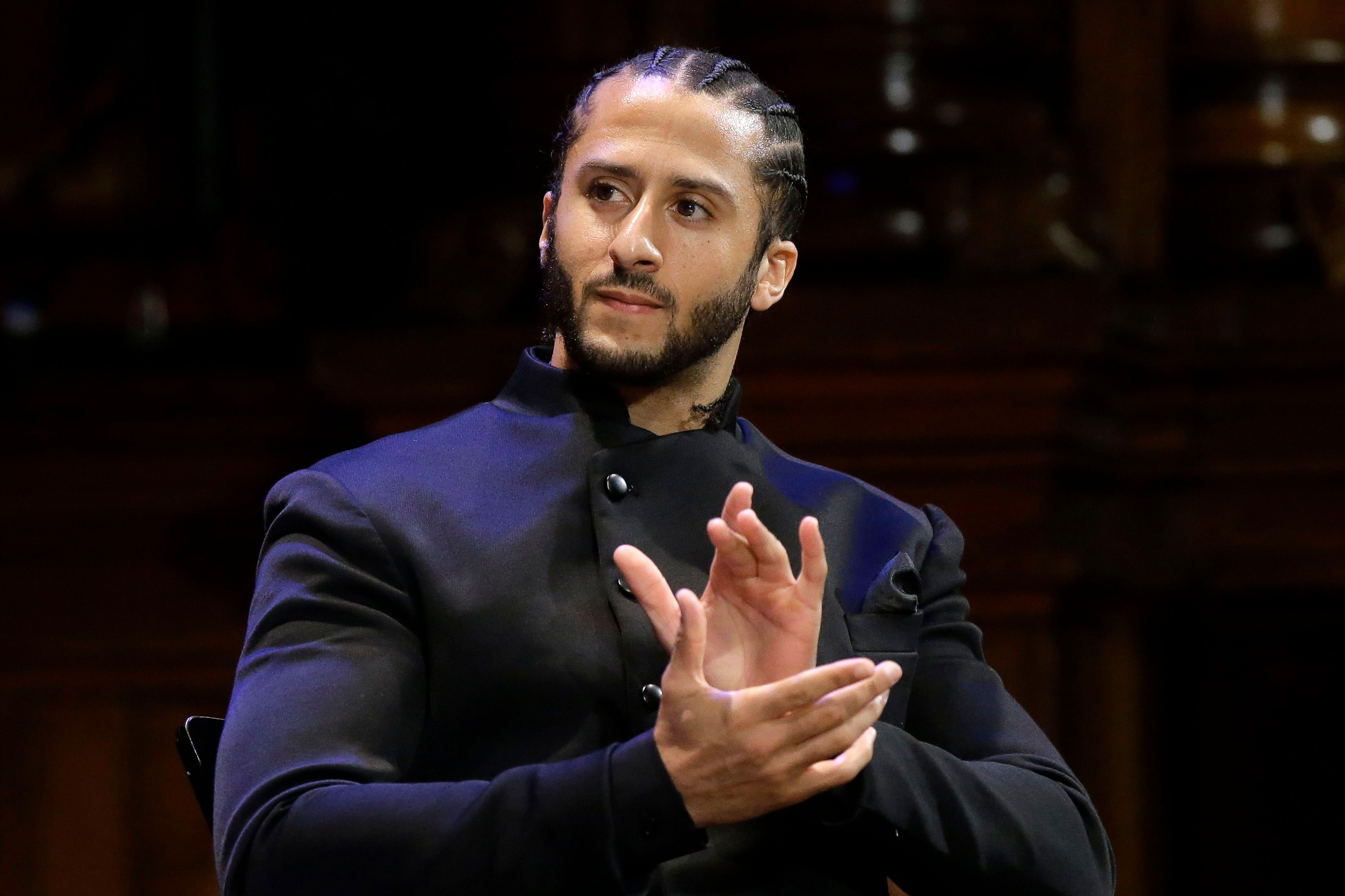 5a844b4cc2b Former NFL football quarterback Colin Kaepernick applauds while seated on  stage during W.E.B. Du Bois Medal