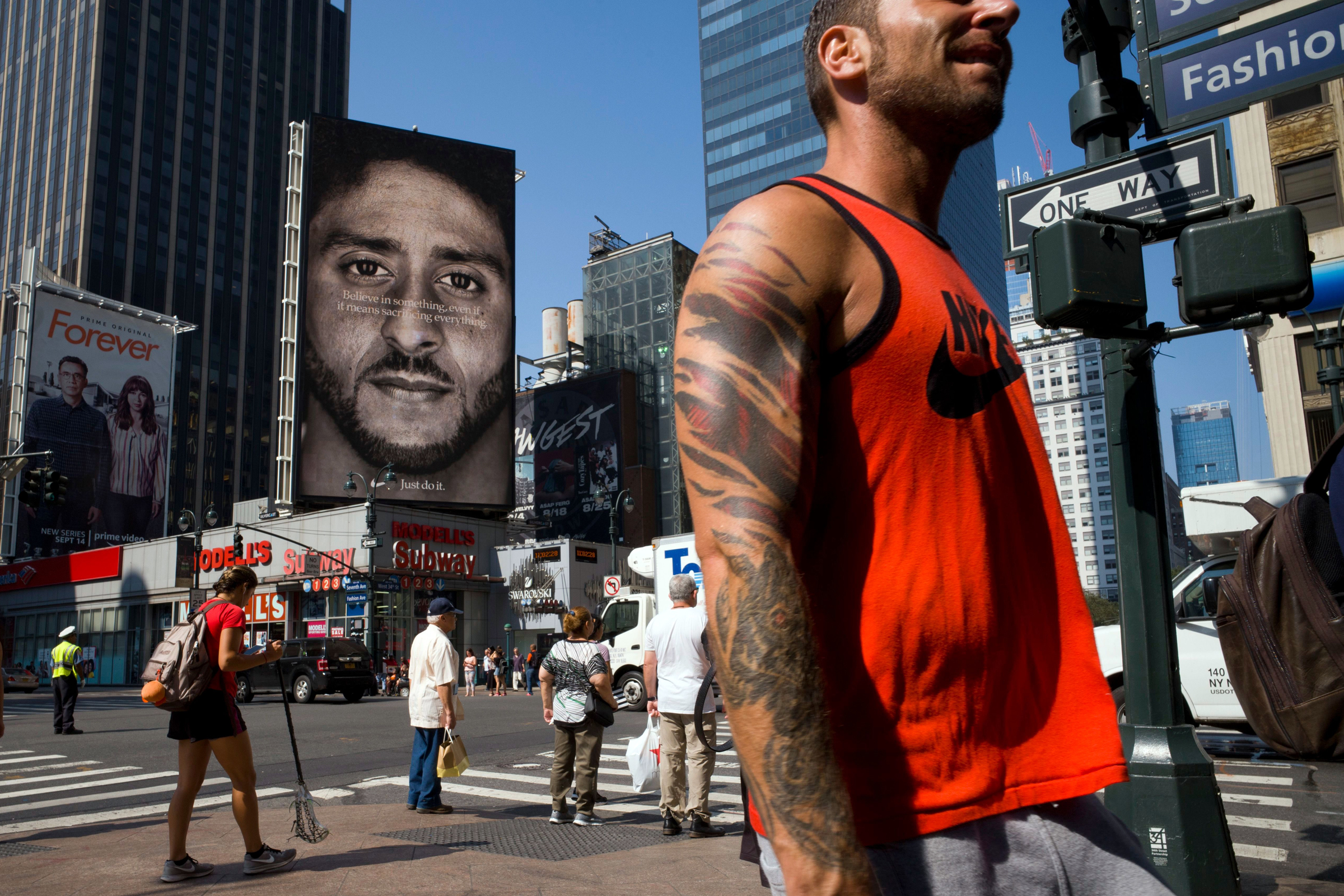 0cb7afd97 People walk by a Nike advertisement featuring Colin Kaepernick on display