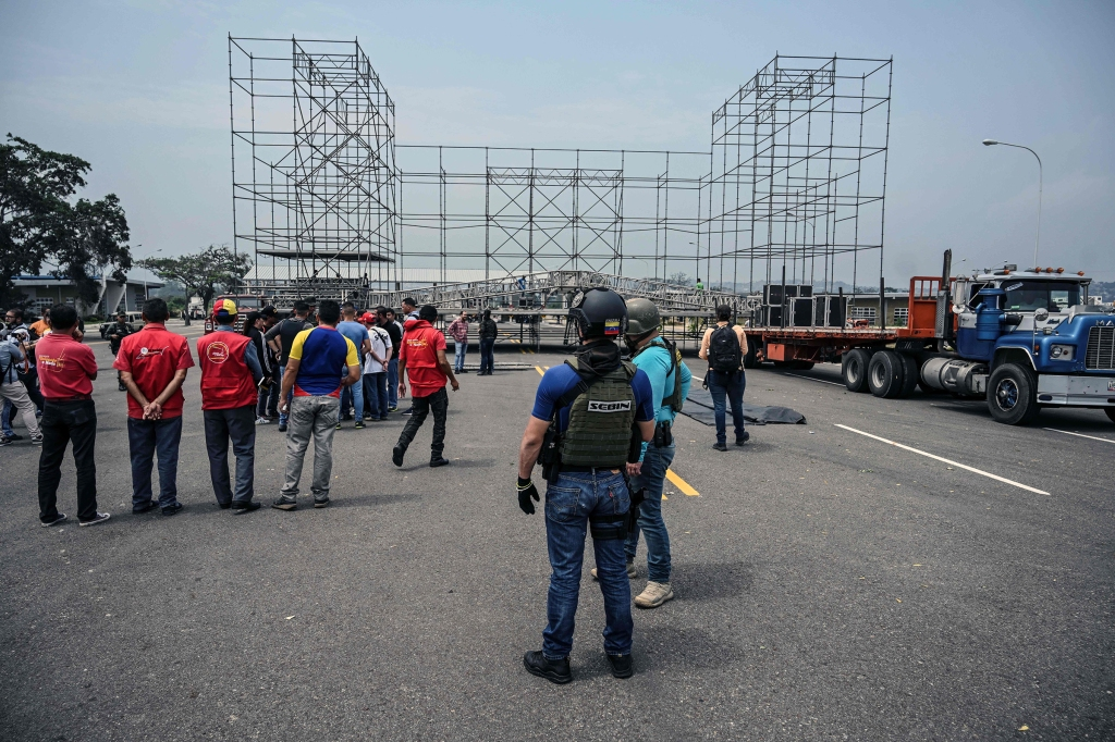 A member of Venezuela's intelligence service (SEBIN) monitors, while workers set up a stage for a concert organized by the government of Venzuelan President Nicolas Maduro on Tienditas Bridge in Tachira, Venezuela, in defiance to the pro-aid concert that backs the initiative of opposition leader Juan Guaido, just on the other side of the bridge in Cucuta, Colombia on February 21, 2019. - Underlining the swell of international support for Guaido, British entrepreneur Richard Branson plans to hold a pro-aid concert just inside Colombia on Friday, while Maduro's government stages a rival concert on its side of the border, around 1,000 feet (300 meters) away. (Photo by Juan BARRETO / AFP) (Photo credit should read JUAN BARRETO/AFP/Getty Images)