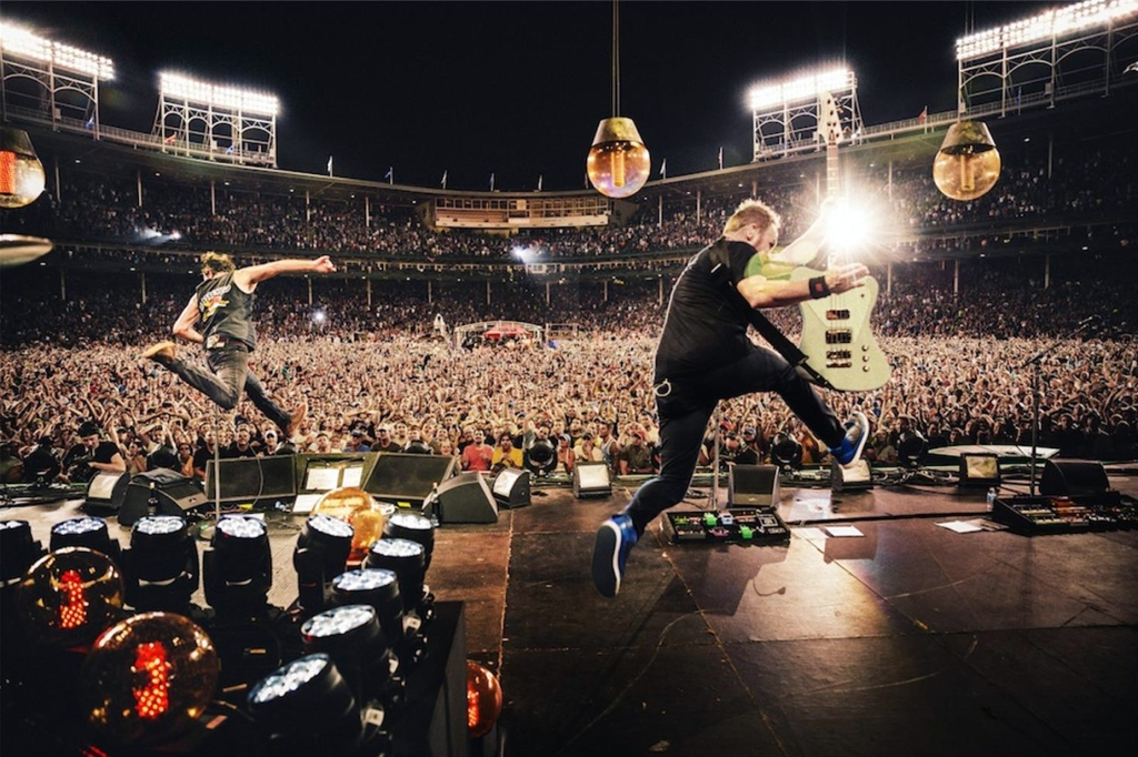 """Pearl Jam performing at Wrigley Field in 2013. """"Relationships with the musicians are important,"""" photographer Danny Clinch tells Rolling Stone. """"They allow you access to what I call the 'sweet spot' behind the drum kit or amplifiers, so that I can grab the moment that shows the connection between the musicians, the audience and the venue, no matter how big or small."""""""