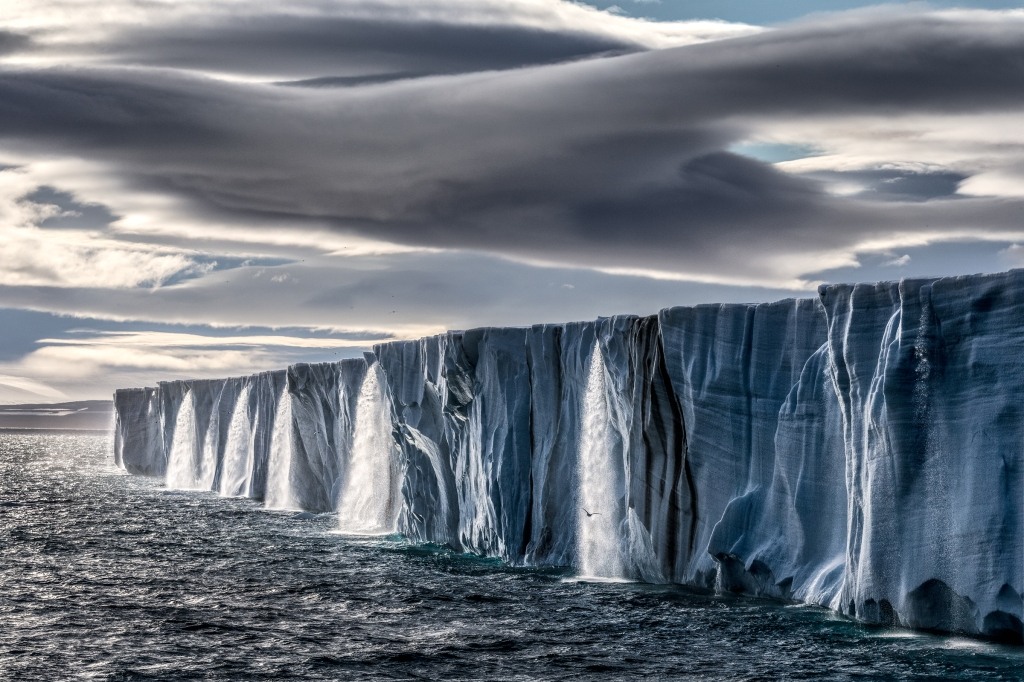 """The Nordaustlandet ice cap in Svalbard, Norway, in the summer. """"Ice caps melt in warmer times of year, but everything is accelerated — water is pouring out full speed now,"""" says Nicklen, who had to postpone photographing polar bears in Svalbard for several years because there was no ice."""