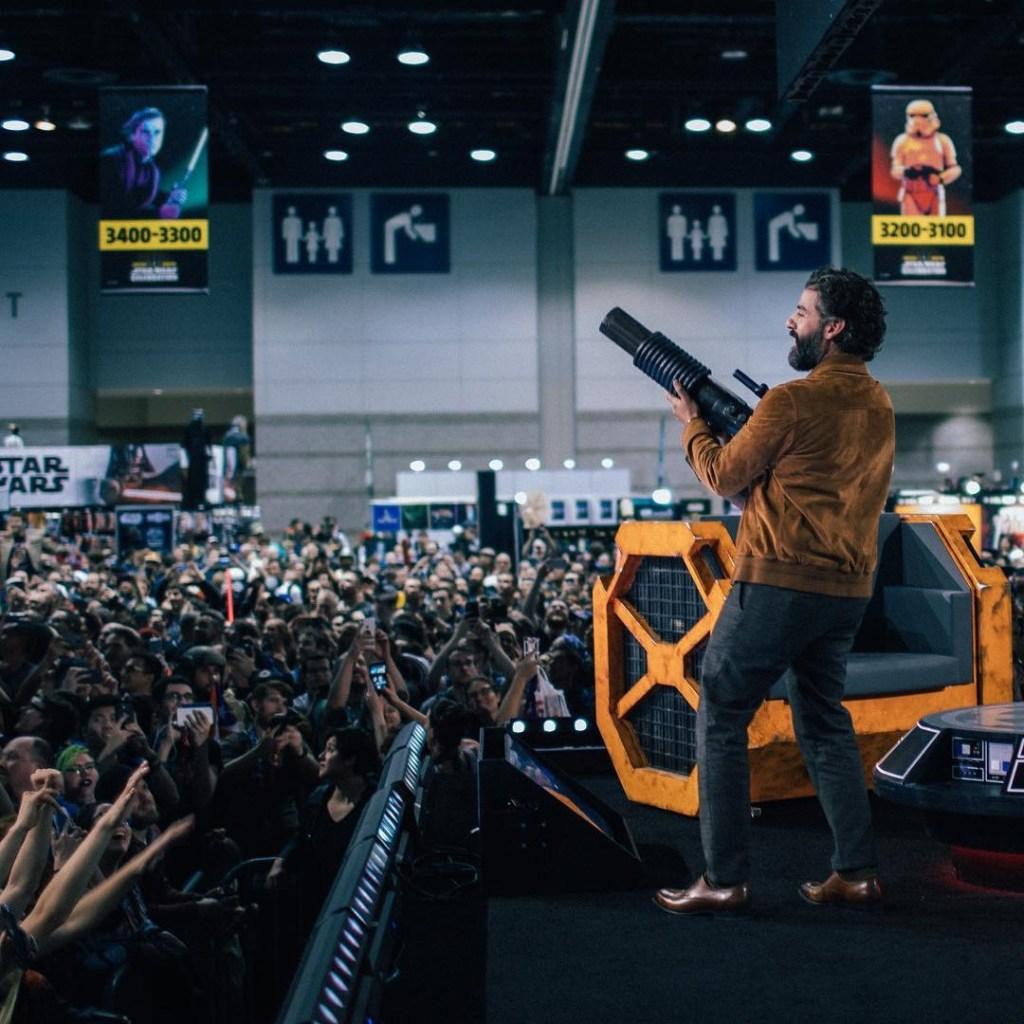 Oscar Isaac fires a t-shirt gun into a crowd of fans