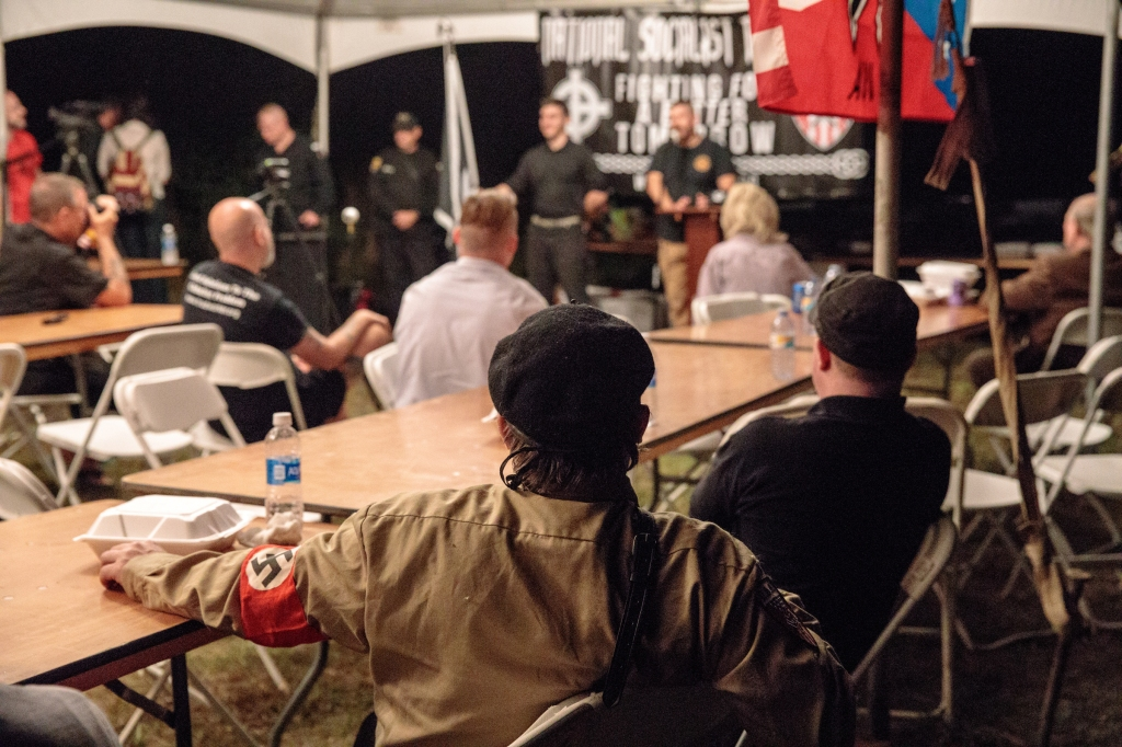 An attendee in a Nazi uniform listens to a speaker. Photo credit: Tod Seelie