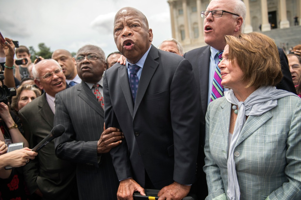 "UNITED STATES - JUNE 23: From left, Reps. Paul Tonko, D-N.Y., James Clyburn, D-S.C., John Lewis, D-Ga., Joe Crowley, D-N.Y., House Minority Leader Nancy Pelosi, D-Calif., Terri Sewell, D-Ala., and Charlie Rangel, D-N.Y., sing ""We Shall Overcome"" with demonstrators on the East Front of the Capitol after the House Democrats' sit-in ended on the floor, June 23, 2016. The Democrats are calling on Republicans to allow a vote on gun violence measures. (Photo By Tom Williams/CQ Roll Call)"