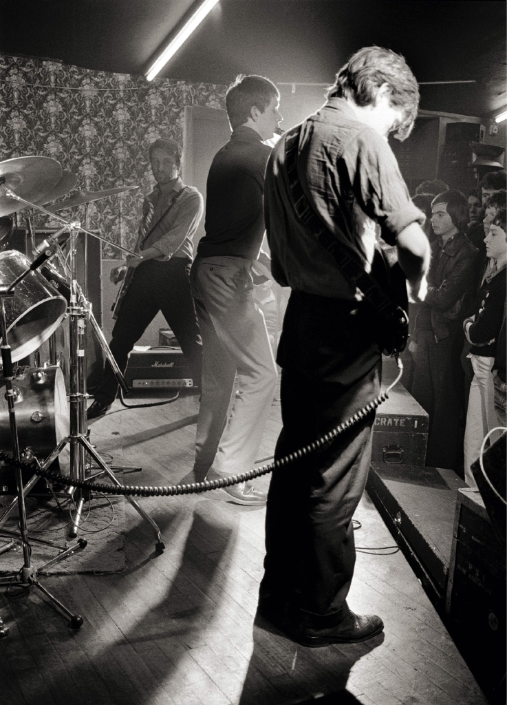 UNITED KINGDOM - MARCH 14: Photo of JOY DIVISION; L-R: Peter Hook, Ian Curtis, Bernard Sumner performing live onstage at Bowdon Vale Youth Club (Photo by Martin O'Neill/Redferns)