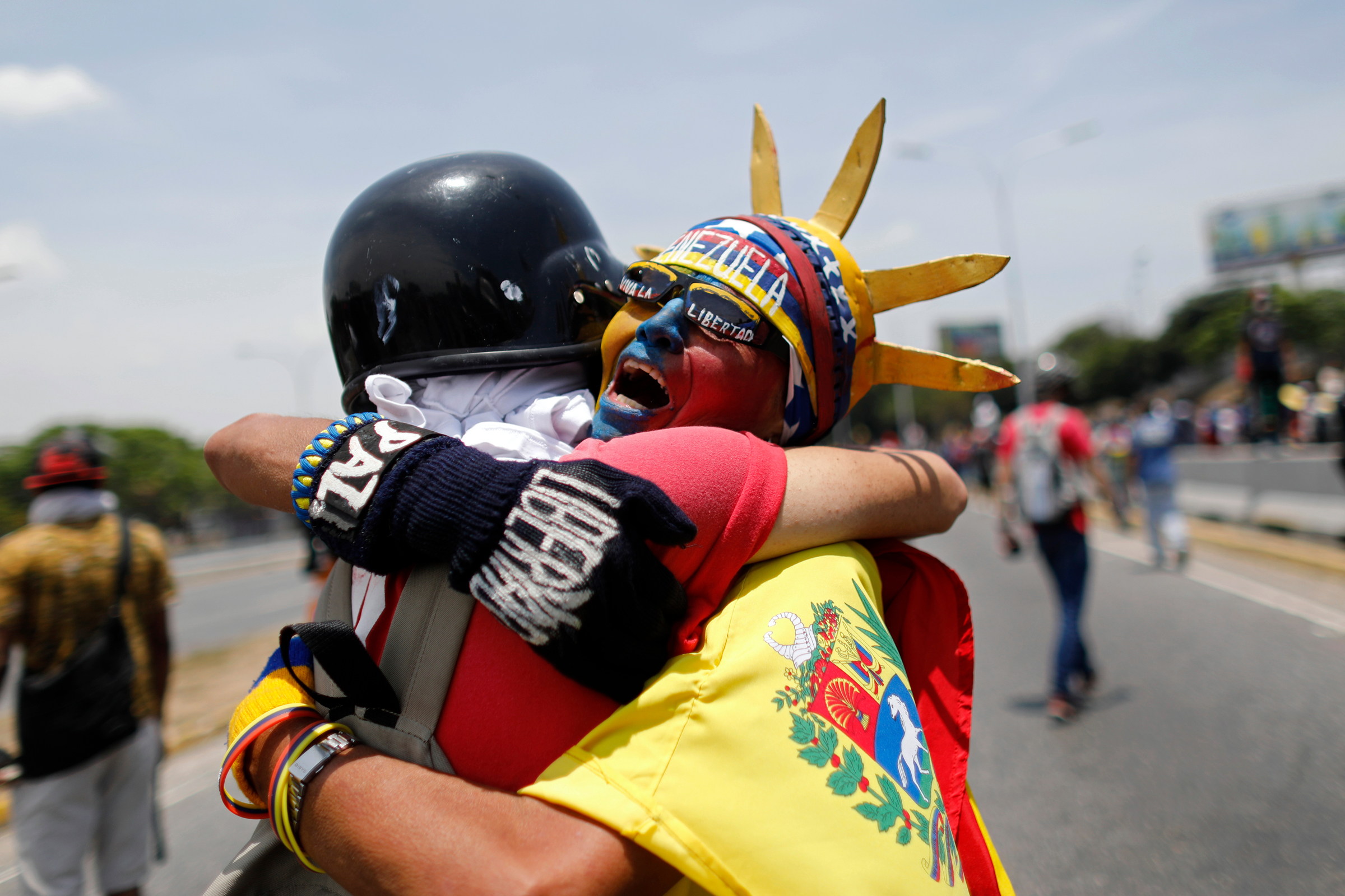 An anti-government protester dressed as Lady Liberty, wearing the colors of Venezuela's flag, hugs a fellow protester during a demonstration near La Carlota airbase in Caracas, Venezuela, . Opposition leader Juan Guaidó is calling for Venezuelans to fill streets around the country Wednesday to demand President Nicolás Maduro's ouster. Maduro is also calling for his supporters to rallyPolitical Crisis, Caracas, Venezuela - 01 May 2019