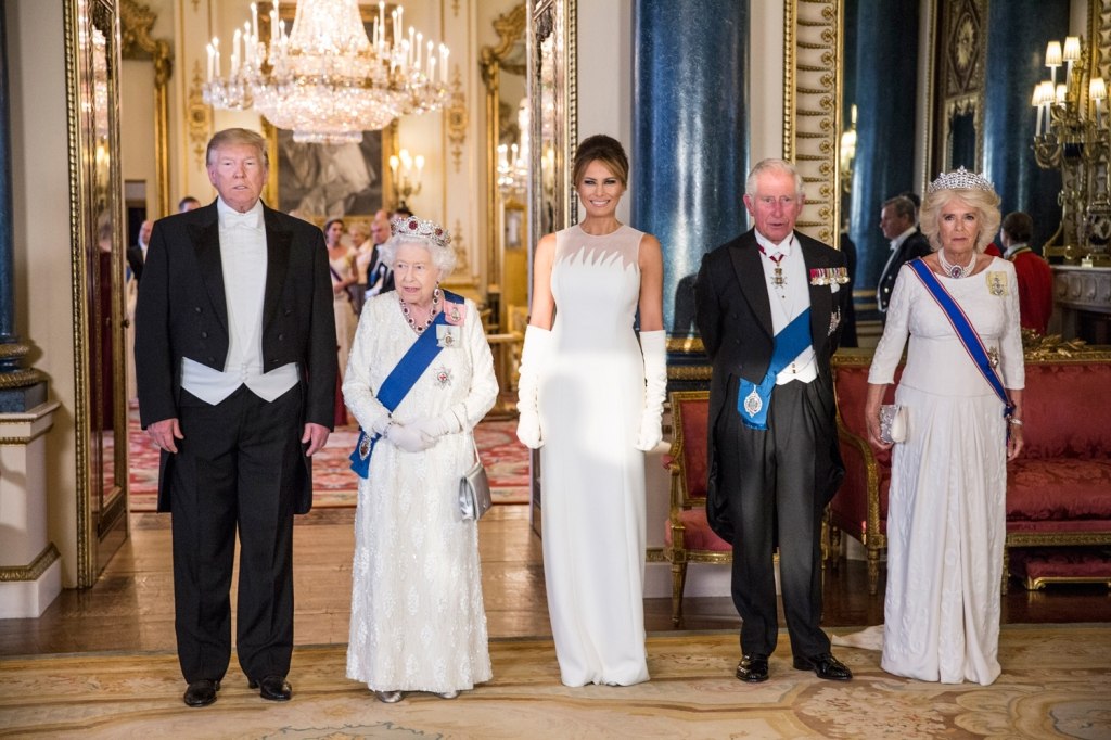 Trump grimaces while posing next to Queen Elizabeth, the first lady, Prince Charles and his wife Camilla.