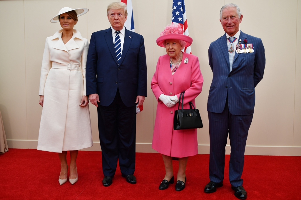Trump appears to signal for off-camera help while standing next to Queen Elizabeth and Prince Charles.