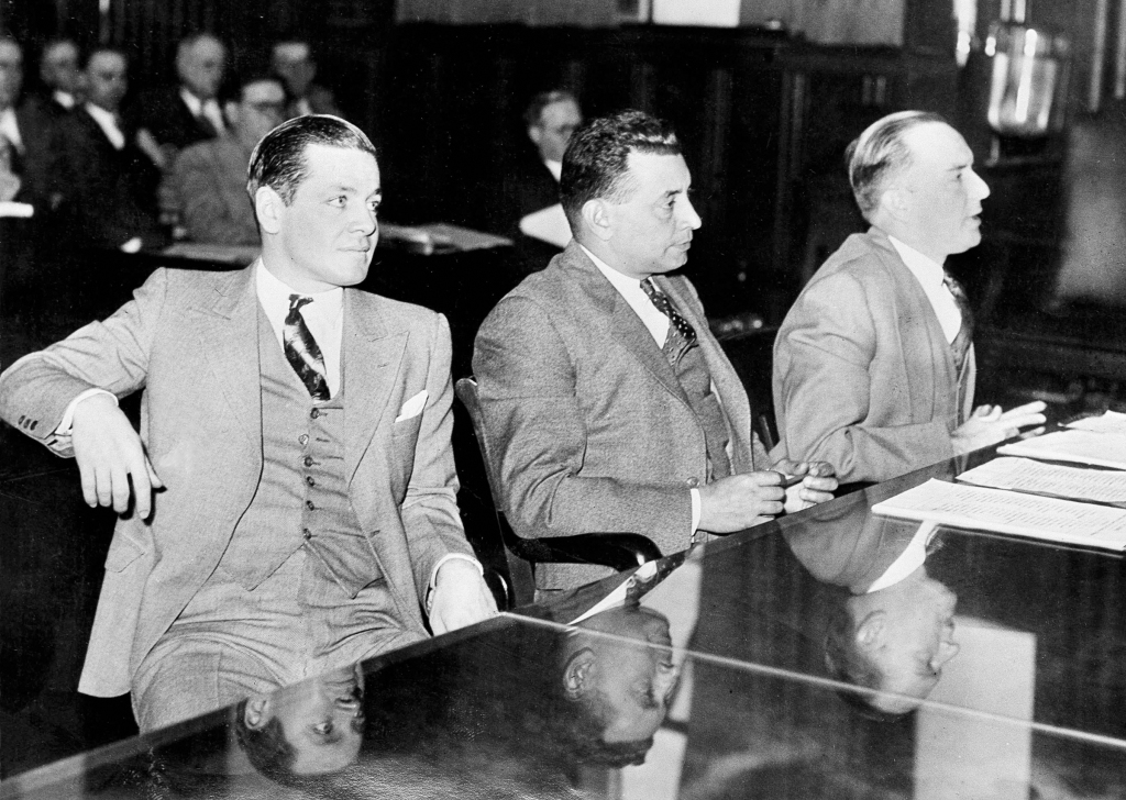 "Louis Kenneth Neu, 26-year-old cabaret singer of Savannah, Ga., left, is pictured on trial, Dec. 15, 1933, in New Orleans for the slaying of Sheffield Clark Sr., a Nashville, Tenn., businessman, in a New Orleans hotel. His attorneys set up an insanity plea for defense but Neu, claiming to be ""perfectly sane"", has repeatedly expressed the wish that ""they would hang me quick and get it over with."" He confessed to beating Clark to death just a week after he had similarly killed Lawrence Shead, a theater manager of Paterson, N.J. Others are unidentified. (AP Photo)"