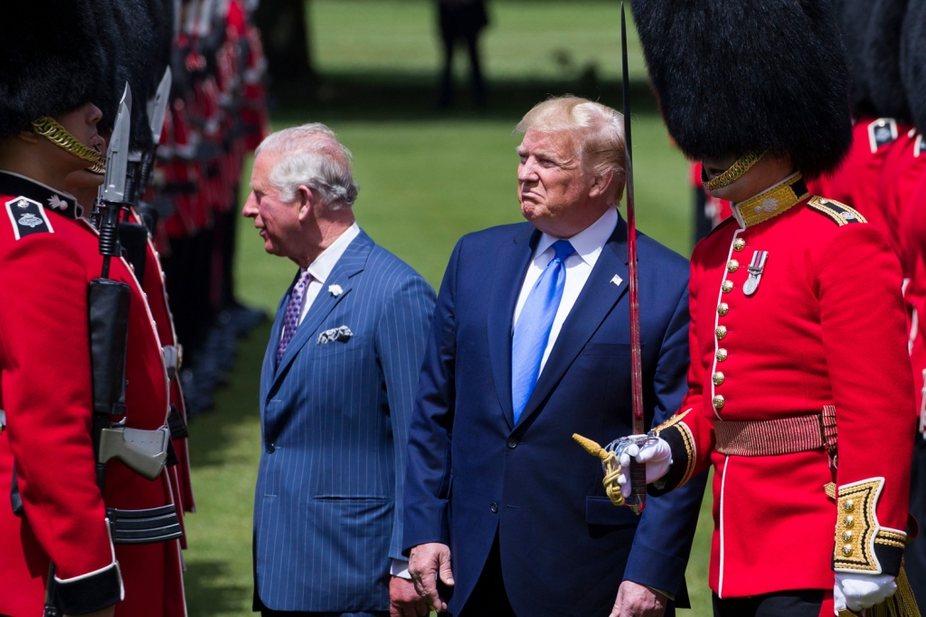 Trump doesn't seem impressed as he inspects the Guard of Honor with Prince Charles.