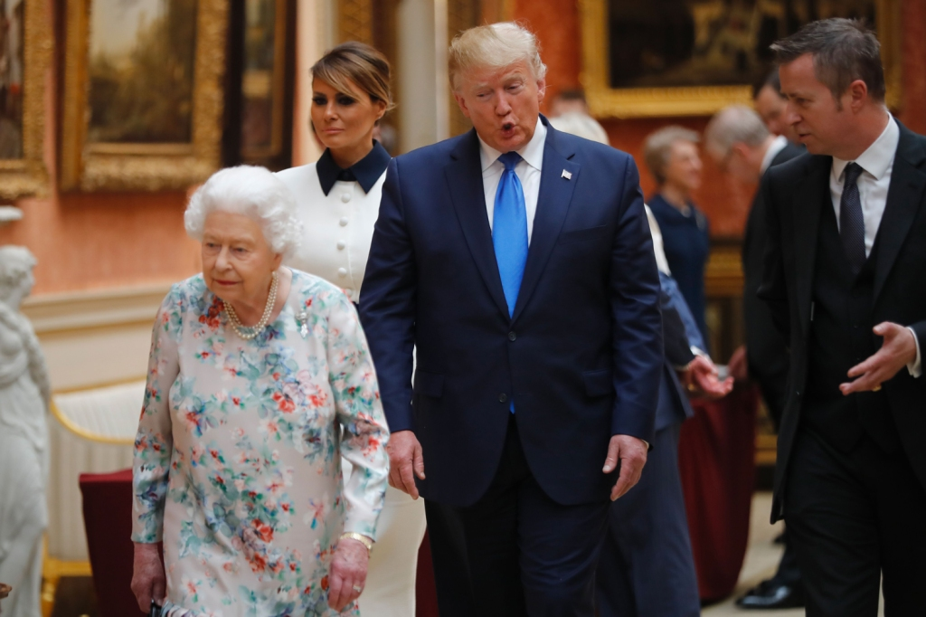 Trump sees something he likes while viewing a display of American items in the Royal Collection at Buckingham Palace.