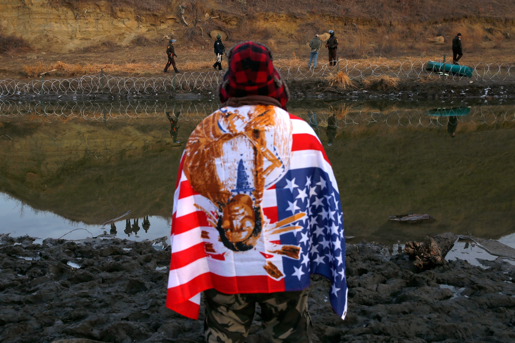CANNON BALL, ND - NOVEMBER 25: A protester watches as police adjust barbed wire that they set up on Turtle Island a day after protesters built a bridge to access it in Cannon Ball, ND near Standing Rock on Nov. 25, 2016, during an ongoing dispute over the building of the Dakota Access Pipeline. (Photo by Jessica Rinaldi/The Boston Globe via Getty Images)