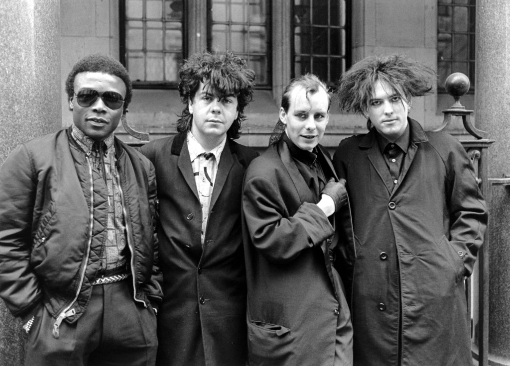 """The Cure – Andy Anderson (Clifford Leon Anderson), Lol Tolhurst, Paul """"Porl"""" Thompson And Robert Smith, 1984."""