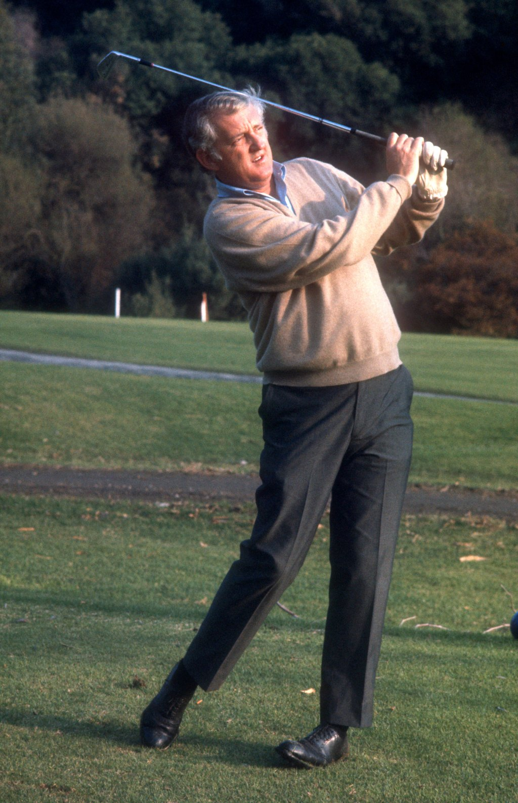 Sports Illustrated writer Dan Jenkins follows his shot during a celebrity golf event circa 1972.