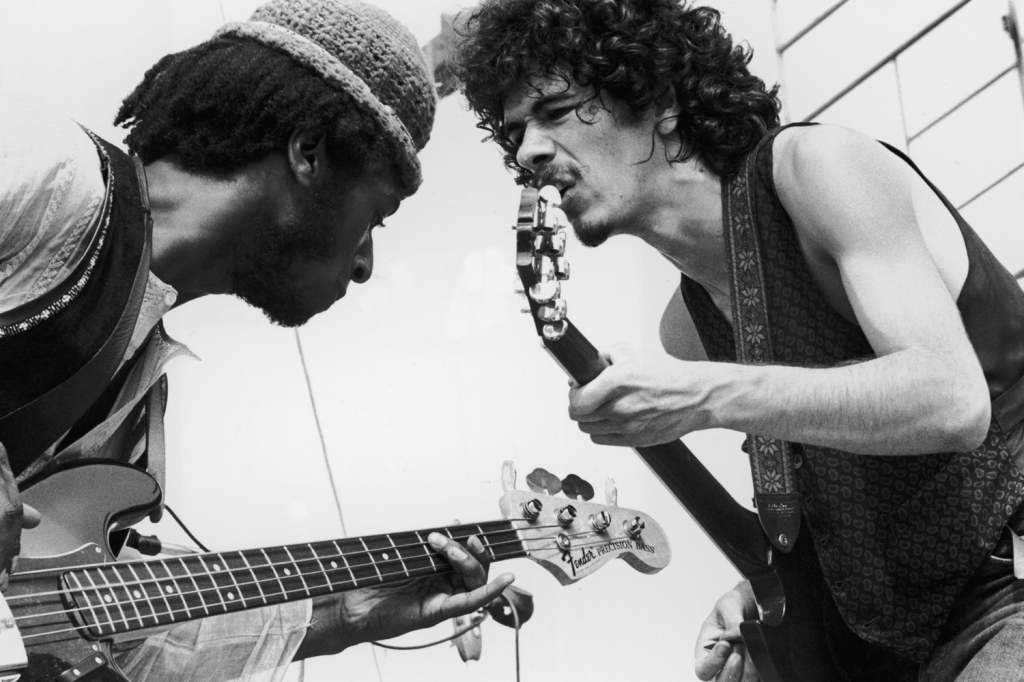 Mexican-born guitarist Carlos Santana (right) and bassist David Brown perform with the group Santana at the Woodstock Music Festival in Bethel, New York.