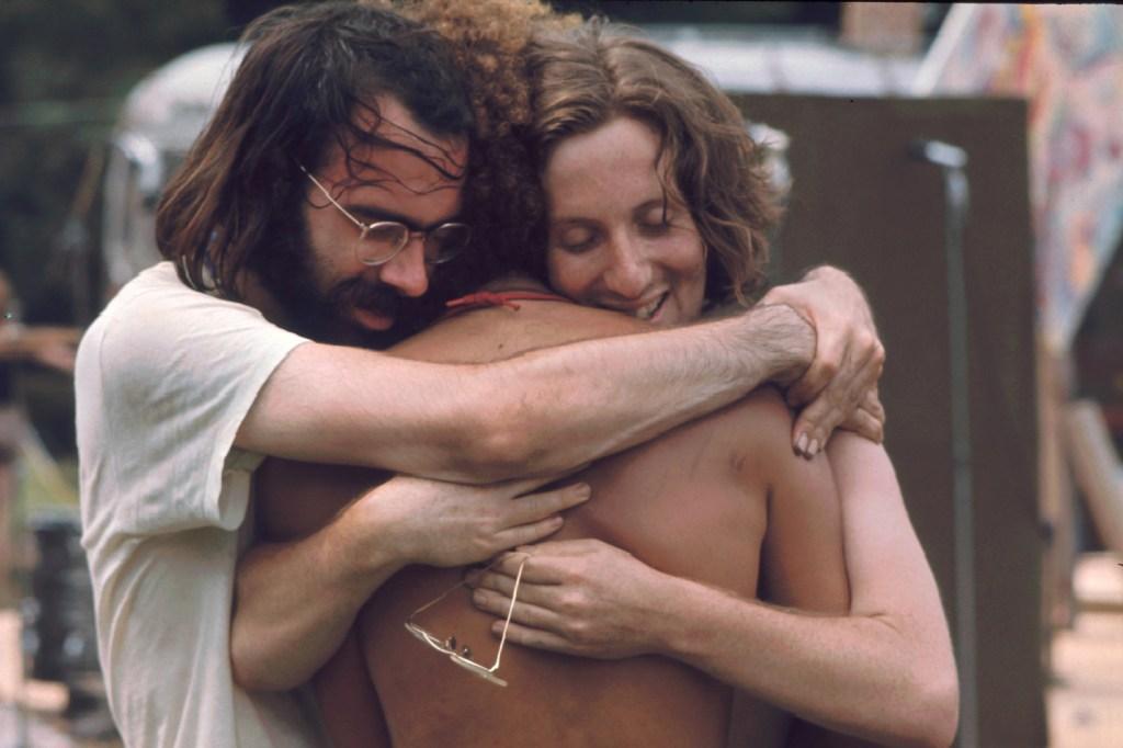 Three men attending the Woodstock music festival hug each other, Bethel, NY, August 1969.
