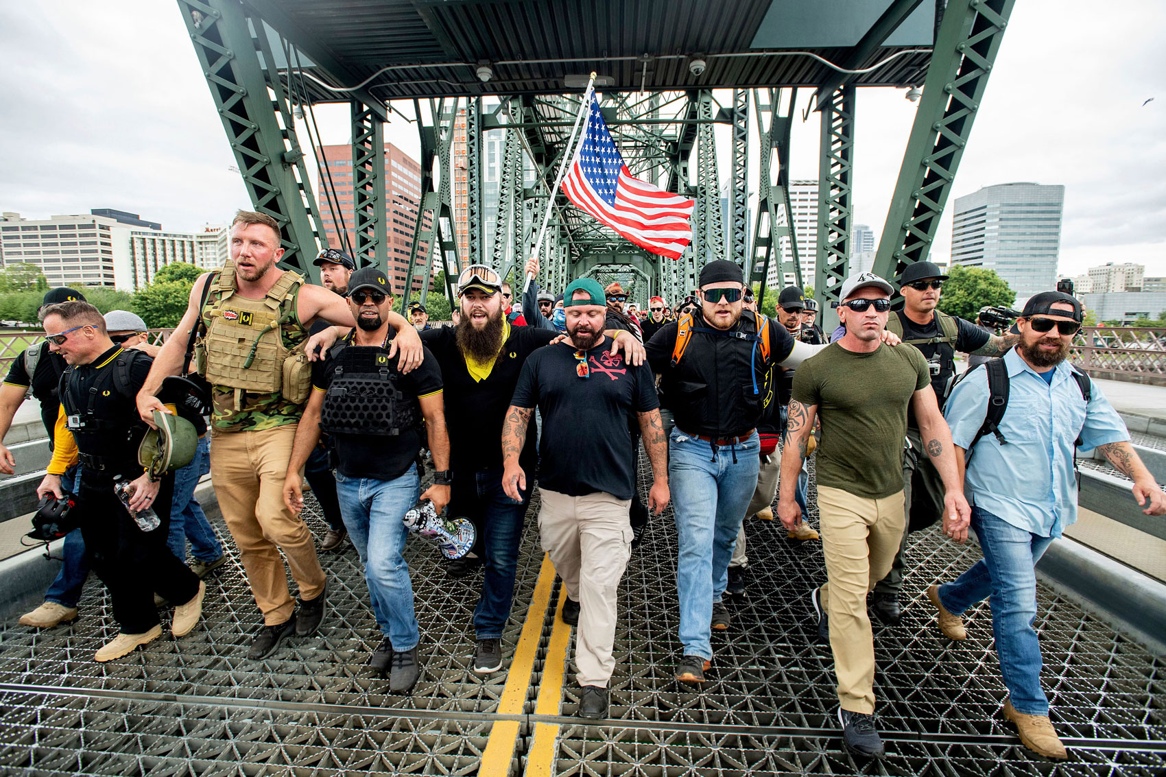 "Members of the Proud Boys and other right-wing demonstrators march across the Hawthorne Bridge during an ""End Domestic Terrorism"" rally in Portland, Ore., on . The group includes organizer Joe Biggs, center in green hat, and Proud Boys Chairman Enrique Tarrio, holding megaphoneRallies, Portland, USA - 16 Aug 2019"