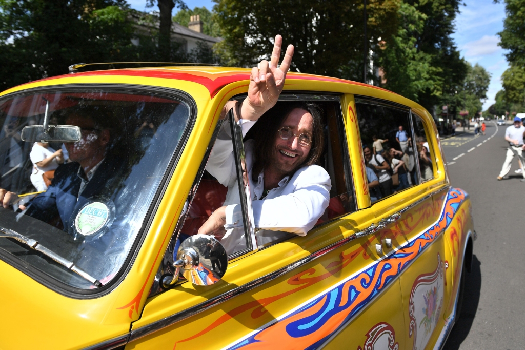 Beatles lookalike band 'Fab Gear' member dressed as John Lennon waves from his replica psychedelic rolls royce after joining fans at the famous Abbey Road zebra crossing in London on August 8, 2019, to celebrate the 50th anniversary of the day that the iconic Beatles album cover photograph was taken.